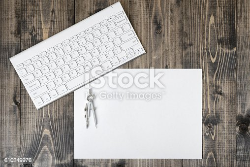 613651130 istock photo Keyboard, paper and compass on wooden plank. 610249976