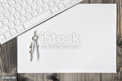 613651130 istock photo Keyboard, paper and compass on wooden plank. 610951796