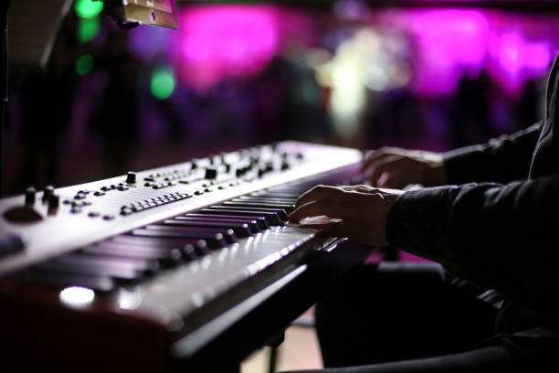 Keyboard player Unrecognizable man playing keyboards on stage during live concert. synthesizer stock pictures, royalty-free photos & images