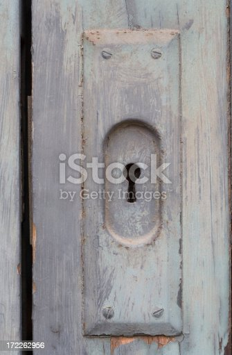 An antique keyhole and cover are shown on a gray door detail
