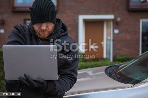 A keyless auto criminal dressed in black with tools of the trade hacking into the security of a car with a laptop in the early morning