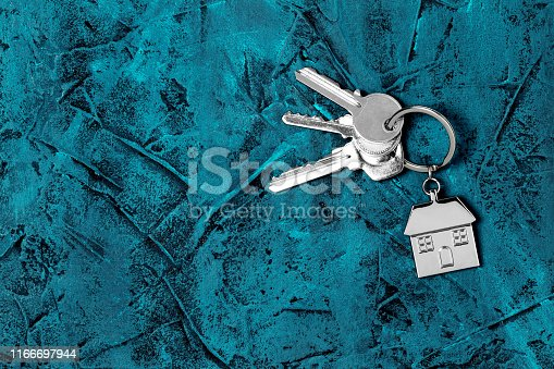 1135927471 istock photo Keys and house keyring / keychain with copy space on blue textured background 1166697944