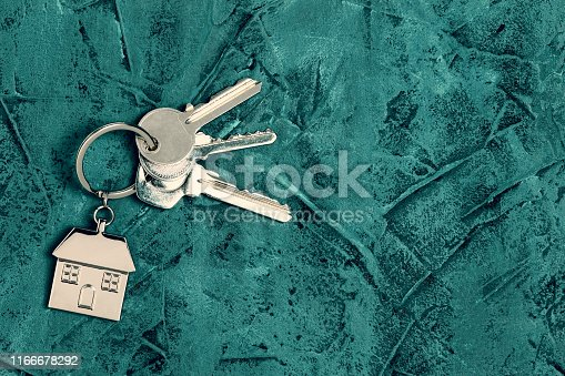 1135927471 istock photo Keys and house keyring / keychain with copy space on turquoise textured background 1166678292