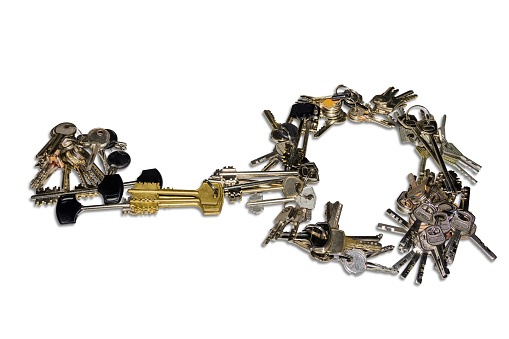 Many bunch of different keys to door locks, laid out in the form of a single large key on a light background. Isolation.