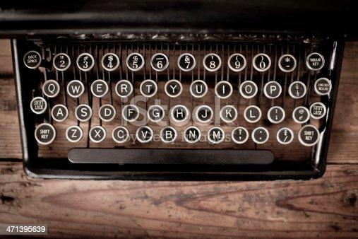 Close up, color image of the keys of a vintage,  black, manual typewriter on wood trunk.