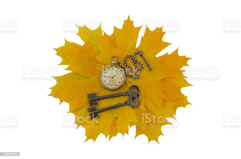 Keys, old pocket watch and yellow leaves. Isolate stock photo