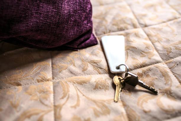 klucze na łóżku hotelowym - motel zdjęcia i obrazy z banku zdjęć