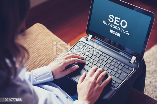 1045434476 istock photo SEO keyword tool in a laptop screen while woman types on the keyboard. 1094077856