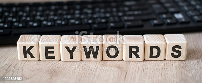 Keywords seo - concept text on wooden cubes and in the background black keyboard