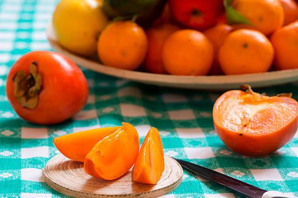 khaki obst scheiben auf einem tisch - sharonfrucht stock-fotos und bilder