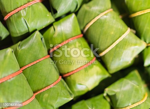 Khao tom - popular Laotian and Thai Dessert. Steamed Sticky Rice with filling wrapped in banana Leaves. Asian cuisine concept image.