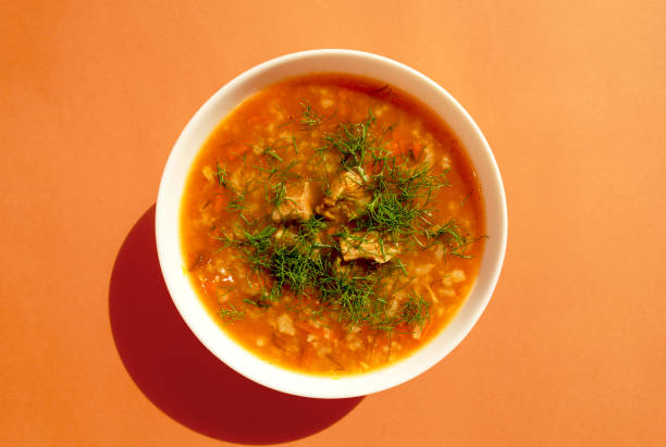 Kharcho soup in a white bowl on a bright orange background. Top view stock photo