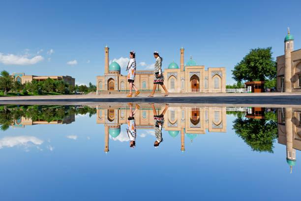 Khast Imam Mosque in Tashkent, Uzbekistan. Tashkent, Uzbekistan - May 18, 2017: Reflection in puddle of water of the Khast Imam Mosque as girls walk in its courtyard, in Tashkent, Uzbekistan. silk road stock pictures, royalty-free photos & images