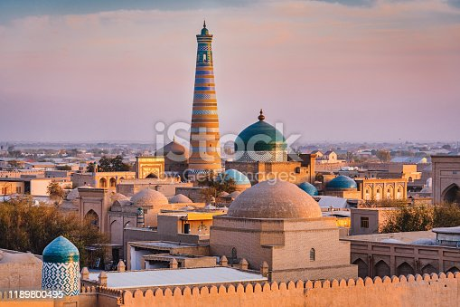 Beautiful sunset twilight over the famous old city of Khiva - Xiva - Хива on the Silk Road with iconic islamic Islam Khoja Minaret - tallest Minaret in Uzbekistan. Itchan Kala, Khiva - Chiva, Xorazm Region, Uzbekistan, Central Asia