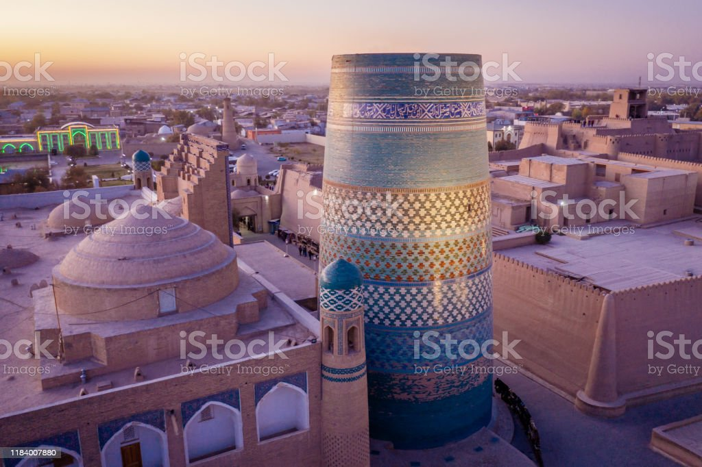 Khiva Sunset Uzbekistan Kalta Minor Beautiful view over the famous city of Khiva with famous iconic Kalta Minor Minaret in the foreground. Aerial Drone Point of View.  Itchan Kala, Khiva - Chiva, Xorazm Region, Uzbekistan, Central Asia Aerial View Stock Photo