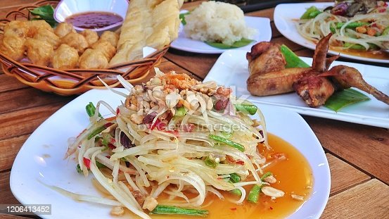 Popular street food in Phnom Penh city, Cambodia. Green papaya salad served with fried meet balls and chicken wings