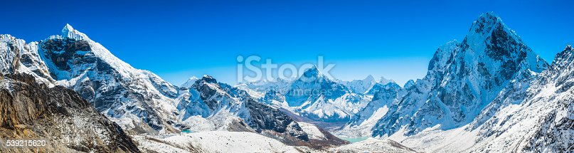 Clear blue high altitude skies over the snow capped peaks, dramatic rocky ridges and soaring pinnacles of the Mt. Everest National Park deep in the remote Khumbu region of the Nepal Himalaya, from the white crest of Lobuche (6145m) to the iconic spire of Ama Dablam (6812m) and the unclimbed north face of Cholatse (6501m). ProPhoto RGB profile for maximum color fidelity and gamut.