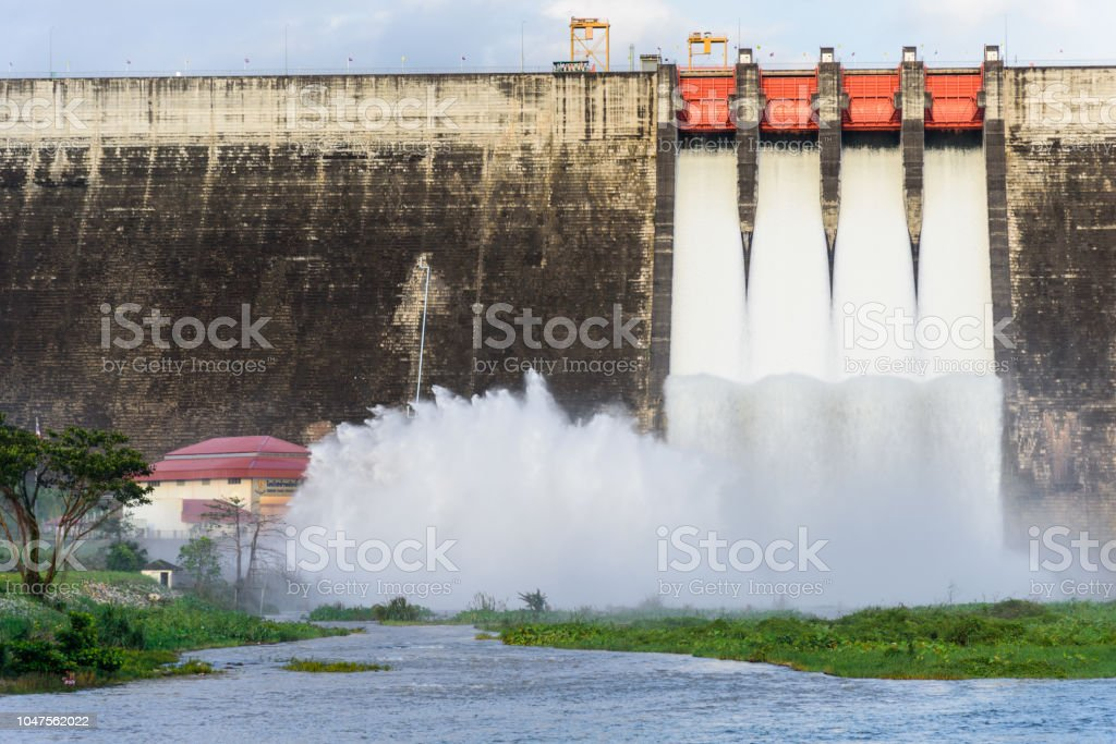 Khun Dan Prakarn Chon Dam has opening the gate for flowing the water in the morning with blue sky backgorund. stock photo