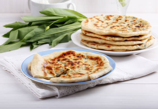 Khychiny - traditional caucasian flatbread filled with heese and herbs.  Flat bread stuffed with feta and wild garlic. Khychiny - traditional caucasian flatbread filled with heese and herbs.  Flat bread stuffed with feta and wild garlic. naan bread stock pictures, royalty-free photos & images