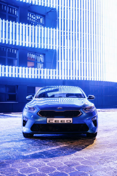 Kia Ceed car in night city against wall with neon color lights stock photo