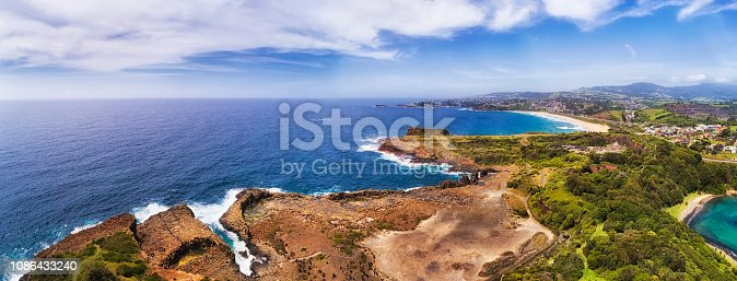 Developed extracted Bombo quarry site in Kiama town - source of hexagonal basalt rocks on pacific coast of Australia in wide aerial panorama.