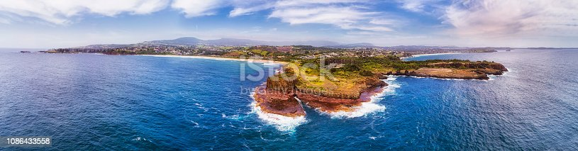 Pacific coast of Australia around Kiama town and Bombo quarry site of hexagonal basalt pinnacle rocks seen from open sea in wide aerial panorama.