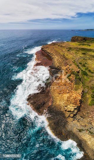 Hexagonal basalt stone pinnacles on waterfront of Bombo quarry site in Kiama town on Australian pacific coast - vertical aerial panorama from water surface to distant horizon.