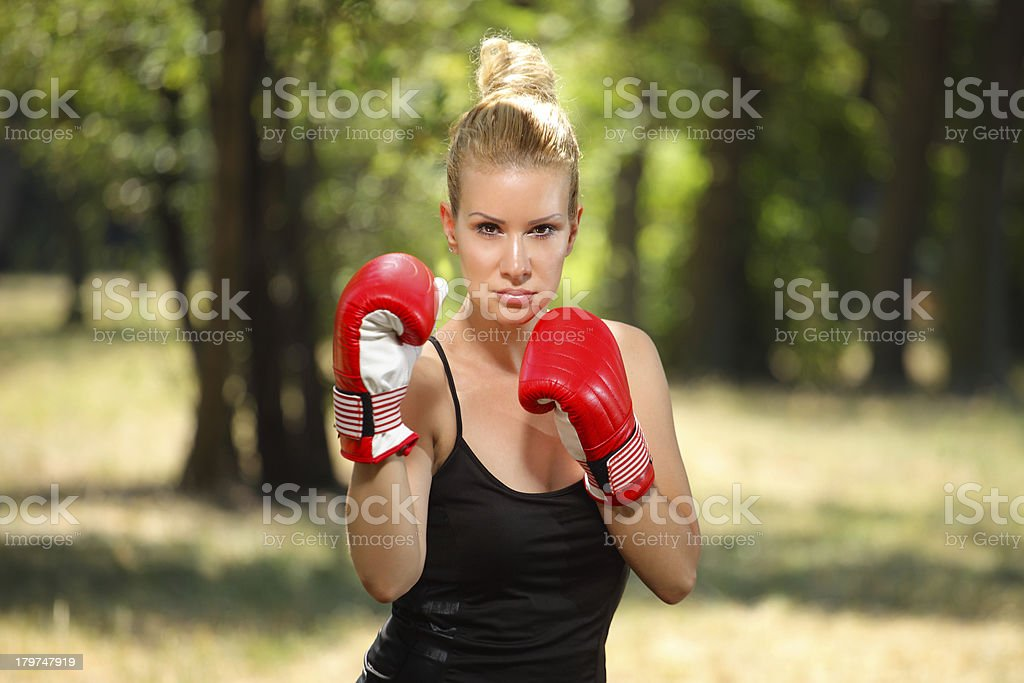 Kick boxing girl exercising in the nature. royalty-free stock photo