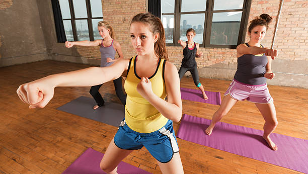 Kick Boxing Martial Arts Exercise Woman Sport Group Workout Training Subject: A group of young teen women practicing kick boxing, stretching and yoga workout exercise together in a health club gym training class session. self defense stock pictures, royalty-free photos & images