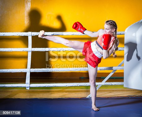 Attractive girl teenager dressed in sports uniform during a fight kickboxing. The girl standing in boxing stance sideways to the camera. She is doing boxing kick to the shadow of man. Shooting in the gym