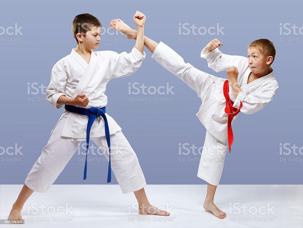 Kick leg and block are doing sportsmen in karategi stock photo