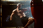 Mid age kickboxer working out in the gym.