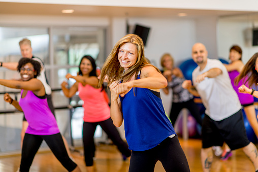 A woman is leading a multi-ethnic boxing class, everyone is wearing athletic clothing and is throwing a punch together - they are smiling and looking at the camera.