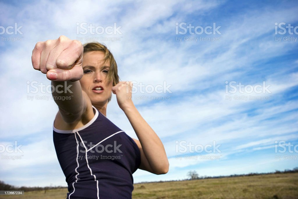 Kickboxing girl forward punching while standing in a field royalty-free stock photo
