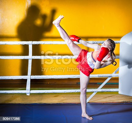 Athletic girl teenager dressed in sports uniform during a fight kickboxing. The girl standing in boxing stance sideways to the camera. She is doing boxing kick to the shadow of man. Shooting in the gym