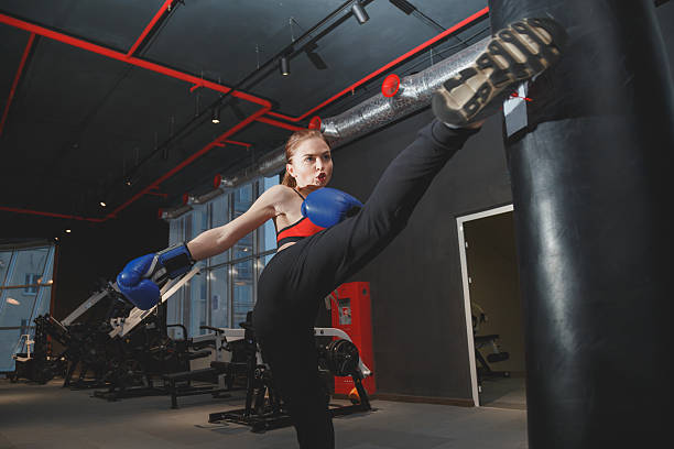 Kickboxing woman punching kicking bag at the gym stock photo