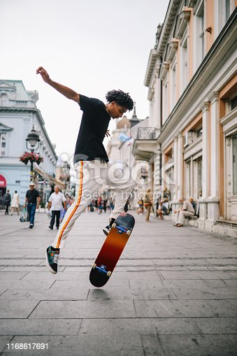 Vintage toned street style fashion portrait of a  young man doing skateboard tricks on the streets of downtown Belgrade, Serbia, Southeastern Europe.
