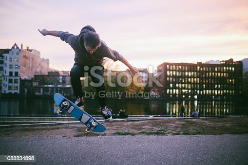 Young man skateboarding in Berlin by the Spree river. He is wearing casual skateboarding clothing, a hoodie and skate shoes, practicing kickflips and other tricks. Taken on a nice Autumn day, just as the sun sets in Berlin's Friedrichshain - Kreuzberg district near the remaining parts of the Berlin Wall.