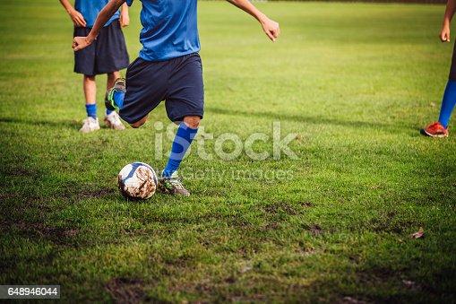 istock Kicking a Soccer Ball 648946044