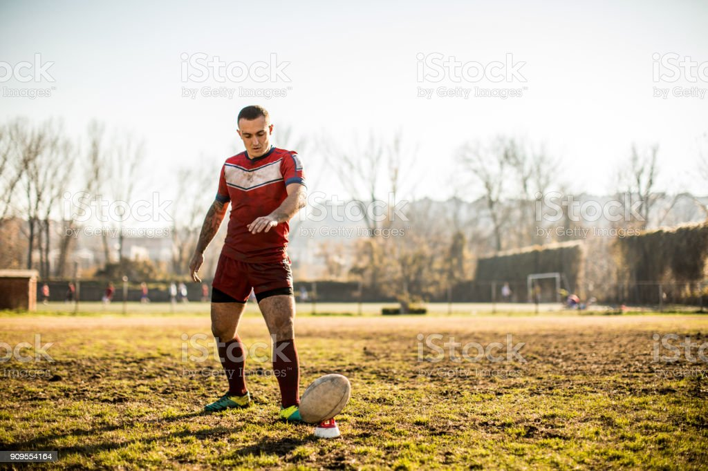 Rugby player kicking the ball,outdoors on a playing field