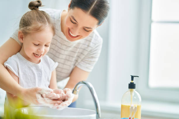 Kid and adult are washing their hands stock photo