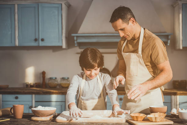 Kid and dad making dish for dessert stock photo