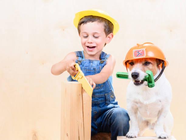 kind und hund tragen schutzhelme mit sah und mit dem hammer auf baustelle - hundezubehör diy stock-fotos und bilder