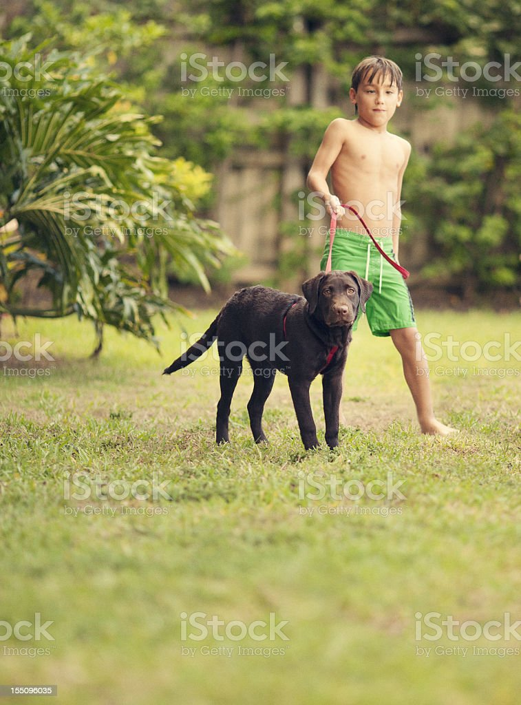 kid and his dog in the backyard royalty-free stock photo