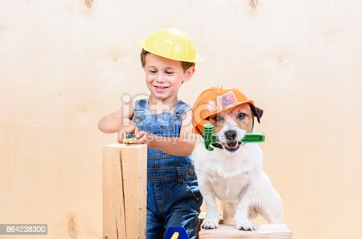 527687520 istock photo Kid and his pet at construction site working as builders 864238300