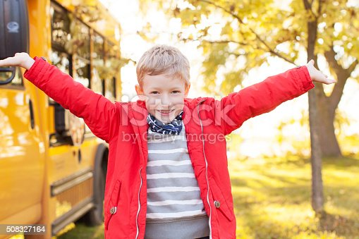 excited schoolboy standing by the school bus ready for new school year
