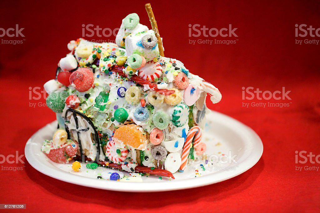 Kid approved messy gingerbread house against red background stock photo