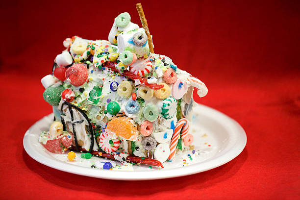 kid approved messy gingerbread house against red background - shabby deko stock-fotos und bilder