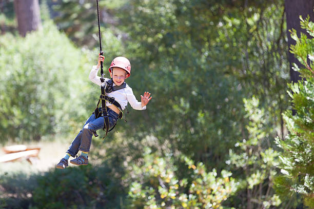 kid at adventure park brave little boy ziplining in adventure park zip line stock pictures, royalty-free photos & images