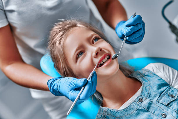Kid at the dentist getting his teeth checked stock photo